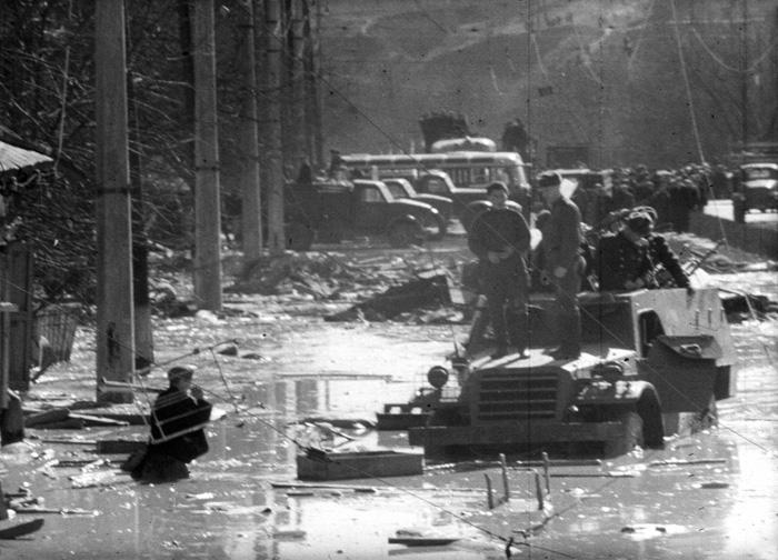 Мужчина выносит к военной машине какие-то пожитки из разрушенного дома
